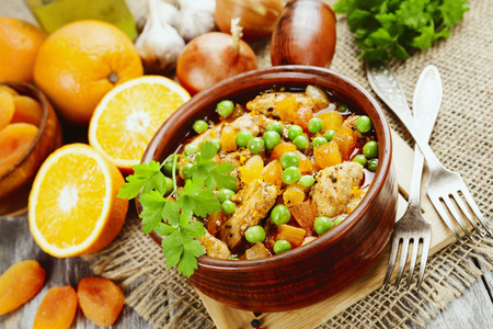 Chicken with oranges, green peas and dried apricots