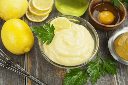 Mayonnaise with olive oil and lemon on the wooden table