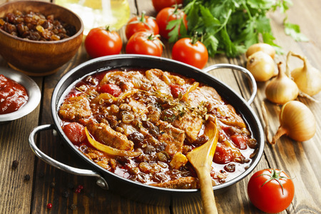 Pork stew with tomatoes and raisins in a frying pan