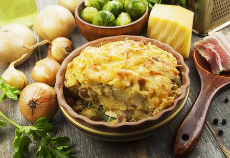 Casseruola di patate con germogli di Bruxelles e pancetta Archivio Fotografico
