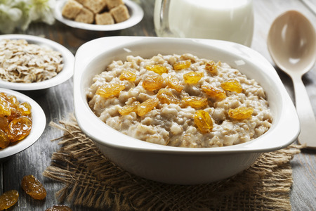 Oatmeal with milk and raisins in the bowl