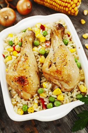 Chicken legs baked with rice and vegetables on the table Banque d'images