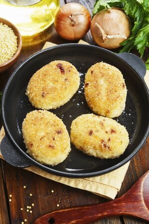 Millet patties in a frying pan on the table