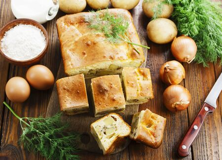 Pie with potatoes and dill on the table