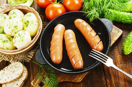 Fried sausages in a pan on the table Stock fotó