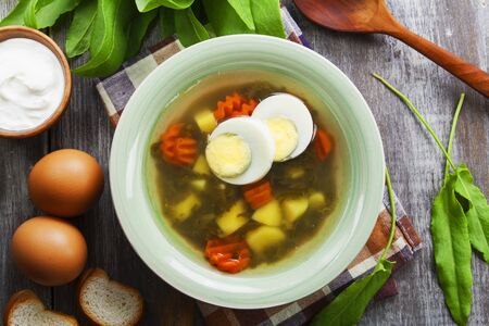 Sorrel soup with egg on wooden table