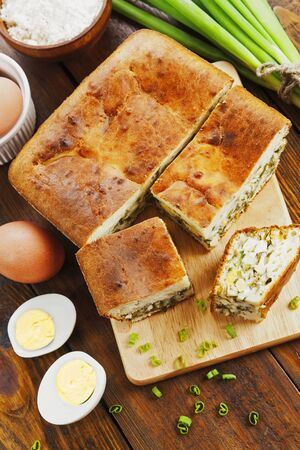 Pie with spring onion and eggs on the table
