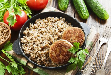 Buckwheat with burgers in a pan on the table Banco de Imagens