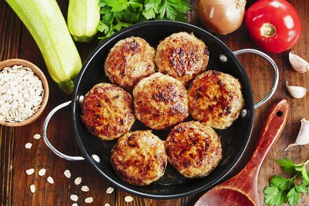 Burgers with oatmeal and zucchini in the pan Stock Photo