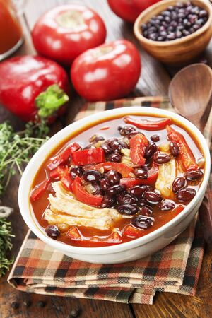 Tomato soup with red beans and meat on the table