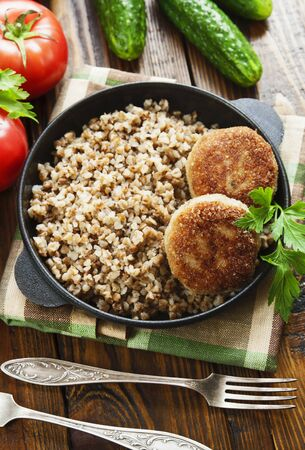 Buckwheat with burgers in a pan on the table Archivio Fotografico