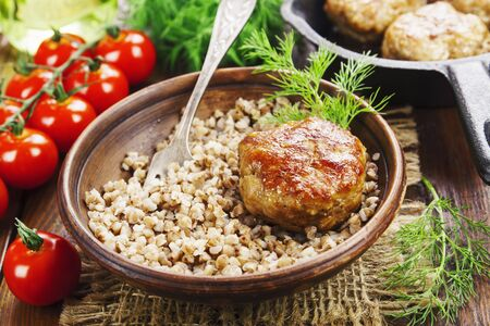 Buckwheat with burgers in a plate on the table