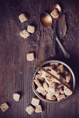 unrefined: Natural unrefined brown sugar in a vintage sugar bowl on old wooden tabletop Stock Photo