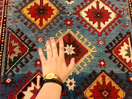 Gentle hand of the woman and oriental carpets. Unique patterns.
