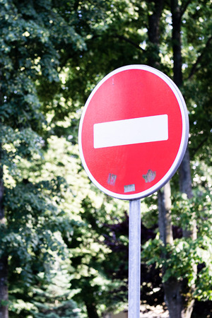 No entrance red traffic sign with green trees in background Stock Photo