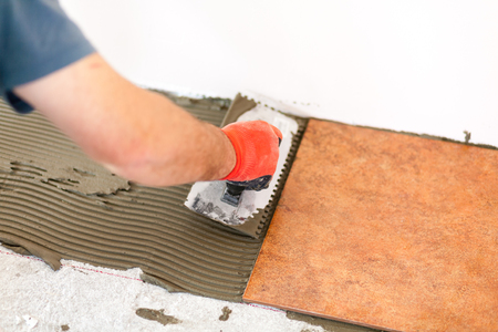 modernize: repairman laying ceramic tiles on the ground