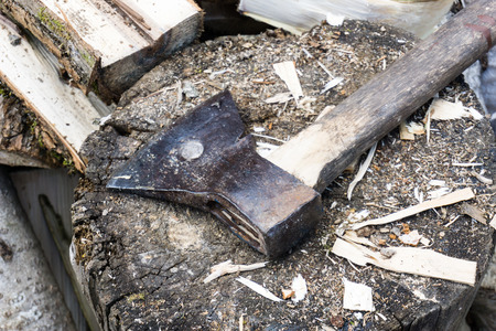 heavy: axe laying on the block with chopped firewood