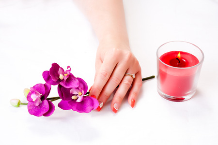 manicure with decor, orchid and red candle isolated on white background. spa Stock Photo