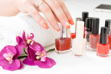 manicure with decor, orchid, towel and polish on white background. spa Stock Photo