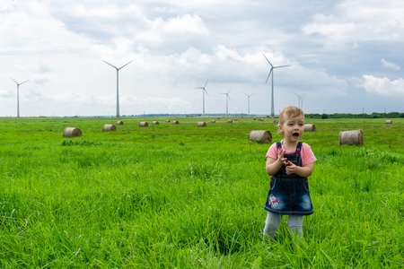 little girl child is standing in green field with hay rolls in front of wind turbine plant farm