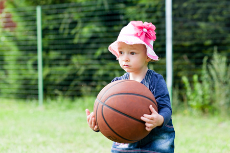 little girl child is playing in the yard with basketball ball