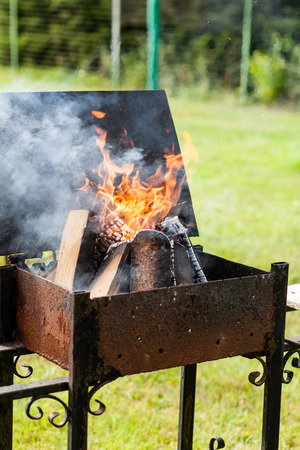 whiff: Flames of burning wood in the metal grill Stock Photo