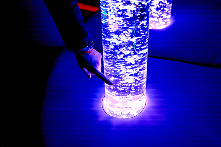 therapy sensory stimulating multi sensory room, woman interacting with colored lights bubble tube lamp during therapy healthcare retirement home session Standard-Bild