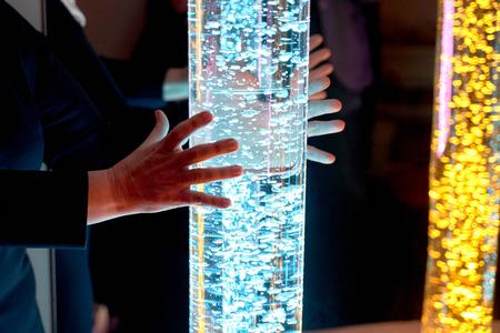 terapia sensorial estimulante sala multisensorial, mujer interactuando con luces de colores lámpara de tubo de burbujas durante la terapia de salud sesión en casa de retiro