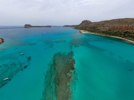 Amazing aerial drone top panoramic view on the famous Balos beach in Balos lagoon and pirate island Gramvousa. Place of the confluence of three seas. Balos beach, Chania. Crete island. Greece. Europe in summer