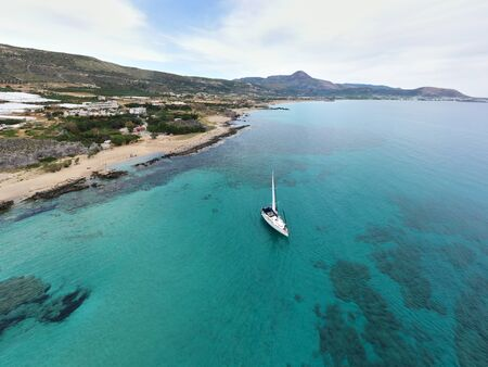 Aerial drone photo of luxury sail boat cruising in the deep blue mediterranean sea, Crete Greece in summer