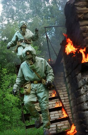 two men in gas-masks running downstairs with the fire near them