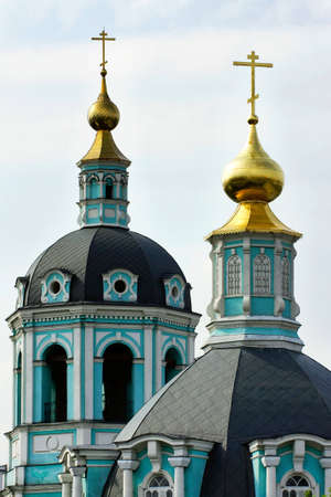 a photo of an Orthodox Church with green walls and golden domes stand behind the trees