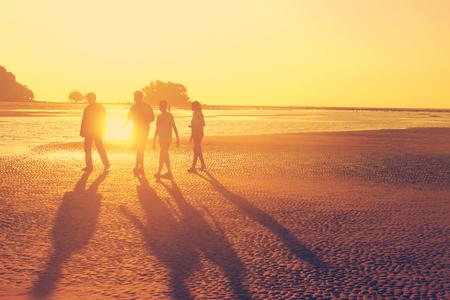 HAPPY FAMILY: La familia caminando en la playa durante la puesta del sol, la luz naranja del sol