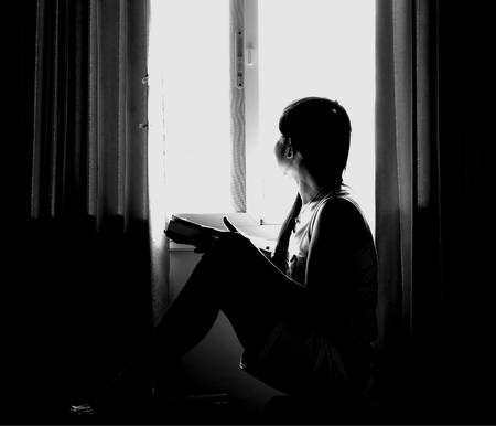 La silhouette di una donna stressata e depressa si è preoccupata per i suoi studi in bianco e nero. elaborato in condizioni di scarsa luminosità