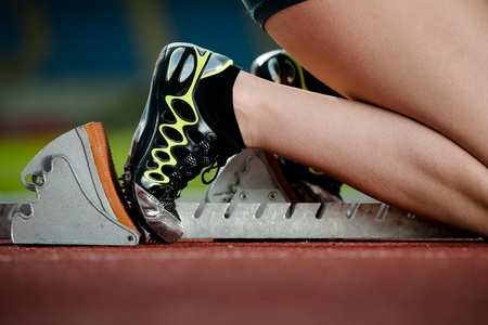 tenseness: Detailed view of a female sprinter in the starting blocks