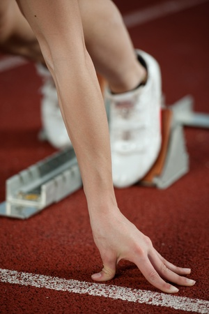 tenseness: Close up view of a female sprinter ready to go