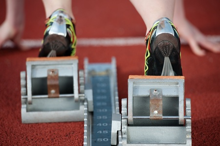 tenseness: Detailed view of a female sprinter wearing sprinting shoes with spikes, leaving starting blocks