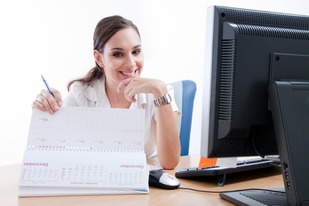 at her desk: Attractive happy young businesswoman behind her desk. Checking her schedule.
