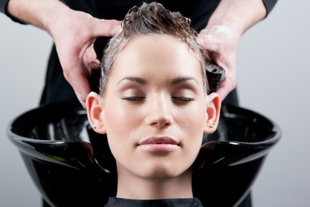 salon: Beautiful young woman getting a hair wash. In a hair salon. Close up.  Stock Photo