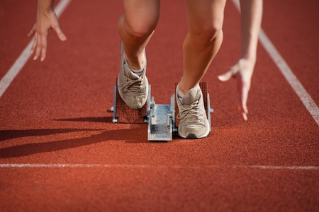 running track: Action packed close-up image of a female athlete leaving the starting blocks for a sprint run on a track  Stock Photo