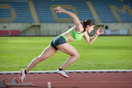 Action packed image of a female sprinter leaving starting blocks on the track. Side view.  Stock Photo