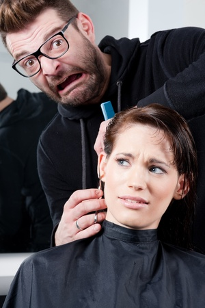 Mad hairdresser about to cut off his clients ear. In a hair salon.  photo