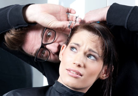Mad hairdresser with a terrified customer. In a hair salon. Selective focus.  photo