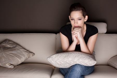 A beautiful young woman watching TV at home alone.  Stock Photo