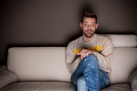 A man with crossed legs watching TV  Stock Photo