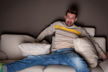 30 to 35: A man watching a scary movie. On the sofa.  Stock Photo