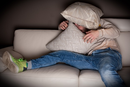A very scared man watching a horror movie at home Stock Photo - 9687922