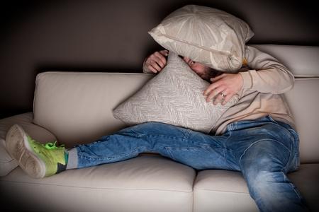 asustado: Un hombre de mucho miedo viendo una pel�cula de horror en casa  Foto de archivo