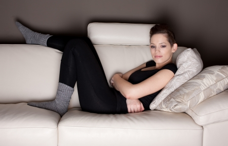 An attractive young woman watching TV, lying on the couch