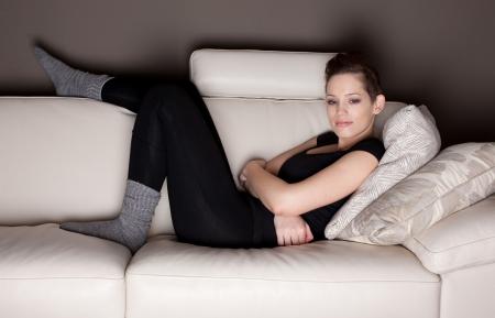 mujer viendo tv: Una mujer joven atractiva, viendo televisi�n, tirado en el sof�